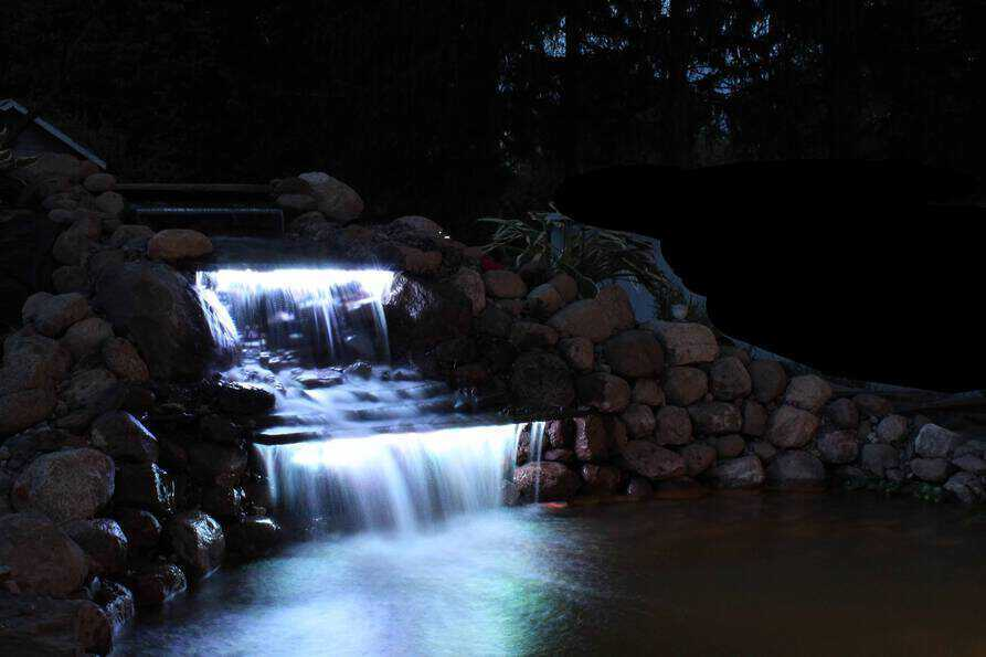 backyard waterfall at night with LED lighting