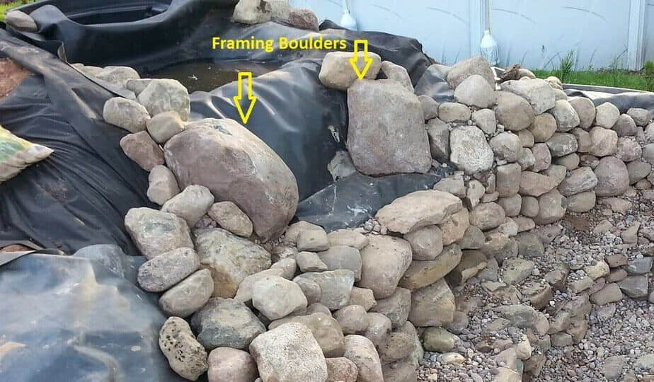 using character boulders to frame in a backyard waterfall